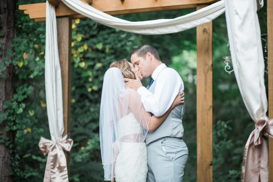 bride and groom kiss at outdoor wedding in Marietta, GA